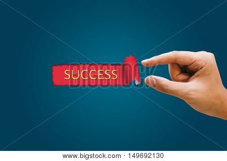 Success concept Businesswomen hand pulling blue paper revealing success text in red background.