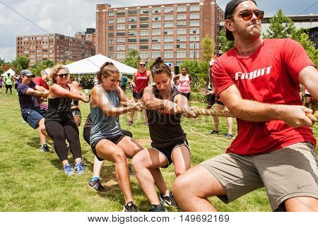 ATLANTA, GA - JULY 2016:  A team of young adults pulls their rope in a tug-of-war contest as part of Atlanta Field Day in the Old Fourth Ward Park in Atlanta GA on July 16 2016.