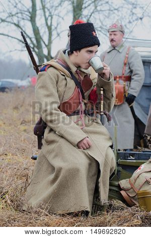 GATCHINA, RUSSIA - NOVEMBER 07, 2015: Young soldiers of the Red Army is drinking tea from a tin cup. International military-historical festival
