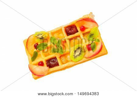 Freshly baked Belgian waffle decorated with fruits. Isolated on white background.