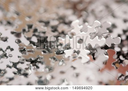 Christmas decoration of silver confetti snow flake against white background with nice boke. Close up confetti with shallow DOF