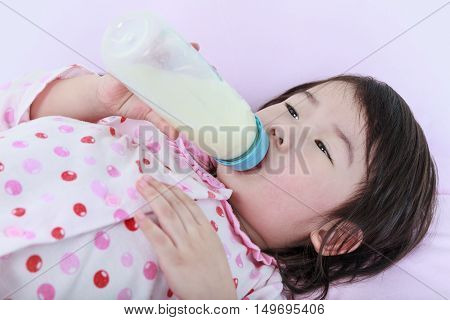Closeup cute asian girl sucking up milk bottle in bed. Drinking milk for good health.