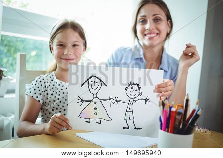 Portrait of mother and daughter sitting at table and daughter showing her drawing