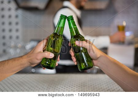 Two men toasting a bottle of beer in bar