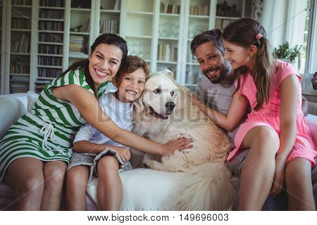 Family sitting on sofa with pet dog in living room at home