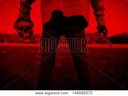 Release evil,Killer with human skull and knife in hand,Scary background for halloween and book cover ideas