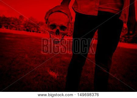 Release evil,Person with human skull in hand,Scary background for halloween and book cover ideas
