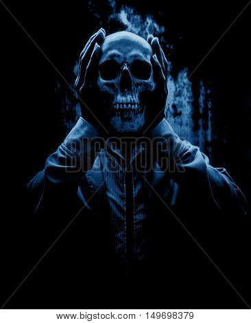Release your evil,Person holding human skull in hand,Scary background for halloween and book cover ideas