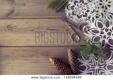 handmade paper snowflakes Christmas tree branches and fir-cones on wooden table