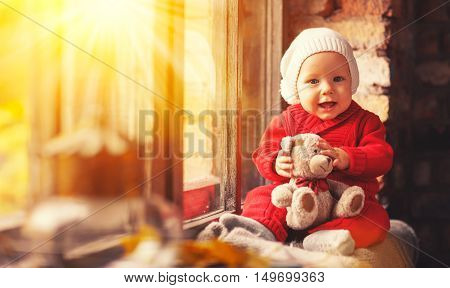 happy baby boy with teddy bear in a red suit about autumn window