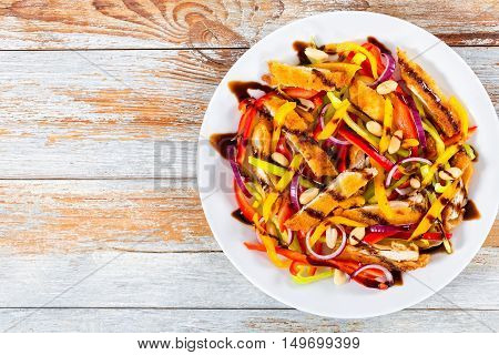 mango bread crumbed chicken meat peanuts bell pepper red onion salad on white dish on white peeling paint boards top view