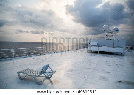 Color image of a beach chair lounger on the deck of a ship under a dramatic cloudy sky.