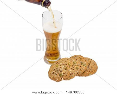 Beer glass with lager beer savory biscuits sprinkled with sesame seeds flax seeds pumpkin seeds and sunflower on a light background