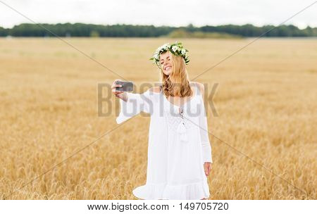 technology, summer holidays, vacation and people concept - smiling young woman in wreath of flowers taking selfie by smartphone on cereal field