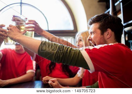 sport, soccer, people and leisure concept - happy friends or football fans clinking beer glasses at bar or pub
