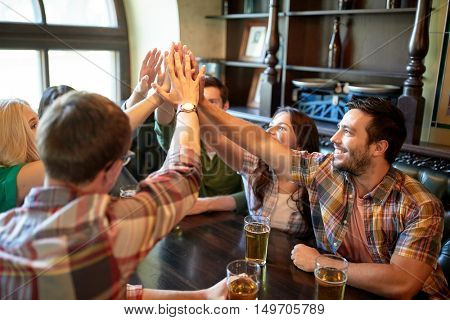 people, leisure, friendship, gesture and communication concept - happy friends drinking beer and making high five at bar or pub