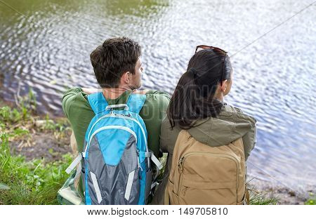 travel, hiking, backpacking, tourism and people concept - couple with backpacks sitting on lake or river bank