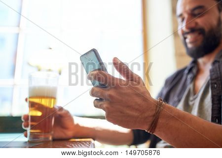 people, leisure and technology concept - close up of man with smartphone drinking beer and reading message at bar or pub