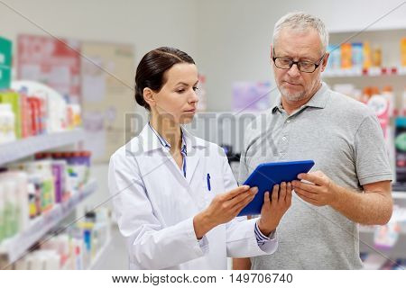 medicine, pharmaceutics, health care and people concept - pharmacist with tablet pc computer and senior man customer at drugstore
