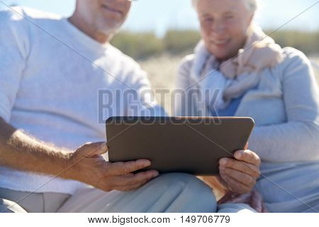 family, age, travel, technology and people concept - close up of senior couple with tablet pc computer sitting on deck chairs on summer beach