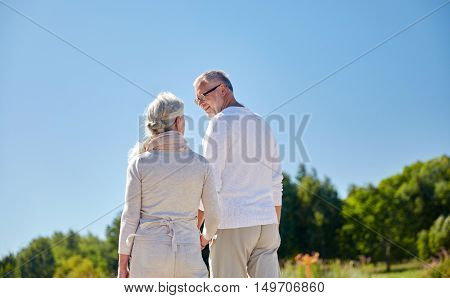 family, old age, leisure, summer and people concept - happy senior couple walking outdoors