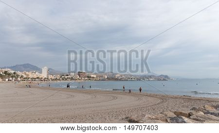 El Campello - October 3 2015: A lovely beach town in the morning and some people relax and bathe in the sea 3 October 2015 El Campello Costa Blanca Spain