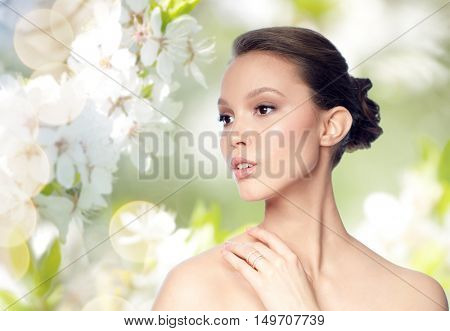 beauty, jewelry, accessories, people and luxury concept - face of beautiful young asian woman with golden ring over natural spring cherry blossom background