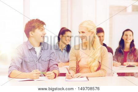 education, school and people concept - two teenagers with notebooks looking at each other at school