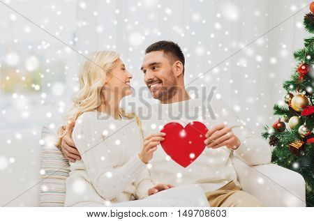 family, christmas, holidays, love and people concept - happy couple with red heart at home