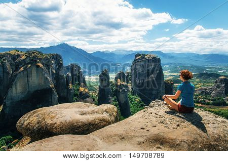 Girl sits on the view point of the mountain and looks at camera concept of travelling happiness freedom. Traveler enjoying the mountain landscape of Meteora Greece