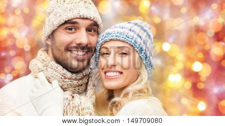 winter, fashion, couple, christmas and people concept - close up of smiling man and woman in hats and scarf hugging over lights background