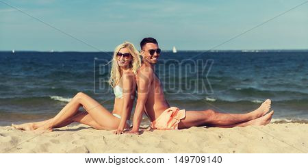 love, travel, tourism, summer and people concept - smiling couple on vacation in swimwear sitting on beach back to back