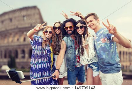 summer vacation, travel, tourism, technology and people concept - smiling young hippie friends taking picture by smartphone selfie stick over coliseum background