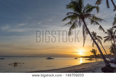 Tropical beach background view from Dumaluan Beach at Panglao Bohol island with cloudy blue sky sundown and palm trees. Travel Vacation
