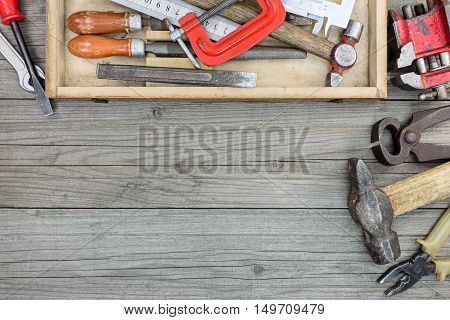 Old Tool Set Of Rusty Hammer, Nipper, Clamps Wrenches And Other Instruments In Toolbox On Wooden Des