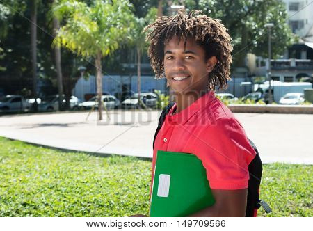 African american male student with amazing hairstyle outdoor in the city in the summer