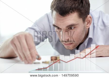 business, people, finances, statistics and money saving concept - businessman putting coins into piles and growing chart