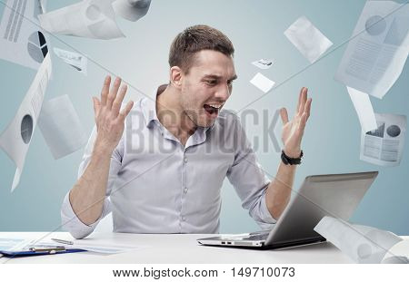 business, people, stress, fail and technology concept - angry businessman with laptop computer shouting over blue background and falling papers