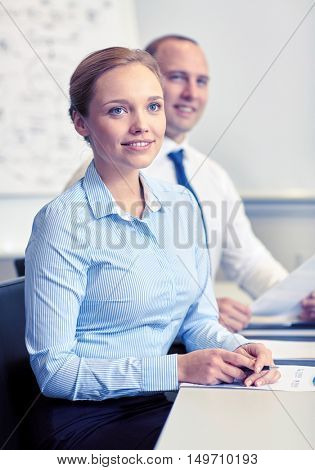 business, people and technology concept - smiling business team with papers meeting in office