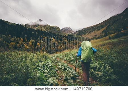 Man hiker with backpack Traveling Lifestyle concept cloudy mountains and autumn forest landscape on background adventure vacations outdoor