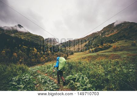 Backpacker hiking Travel Lifestyle concept cloudy mountains and autumn forest landscape on background adventure vacations outdoor