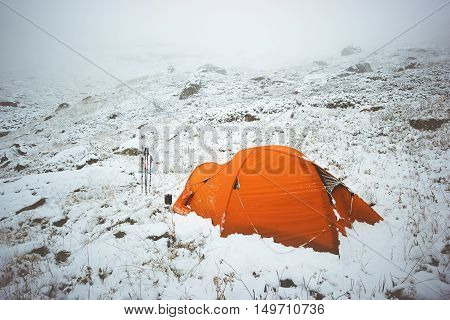 Tent camping in winter mountains foggy snowy weather Travel Lifestyle concept adventure vacations outdoor