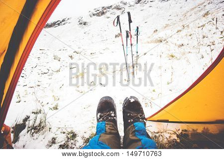 Feet Man relaxing view from tent camping entrance outdoor Travel Lifestyle concept snow mountains on background winter vacations
