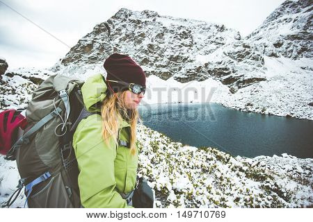 Woman Traveler with backpack hiking Travel Lifestyle adventure concept snow rocky mountains and lake on background winter vacations
