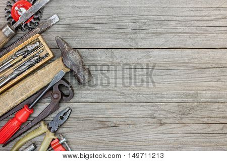 Set Of Various Old Hand Tools Including Hammer Pliers And Nipper On Grey Wooden Planks Background