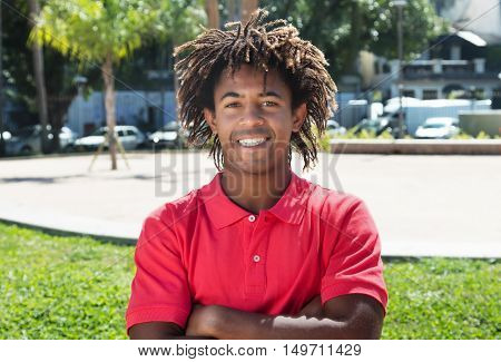 Cool african american guy with amazing hairstyle outdoor in the city in the summer