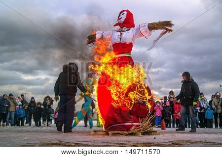 Saint-Petersburg Russia - February 22 2015: Feast Maslenitsa on Vasilyevsky Island. Burning doll - a doll set fire to the organizers. Flame lights up on the skirt.
