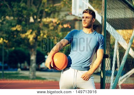 Handsome young man posing with a ball on the basketball court