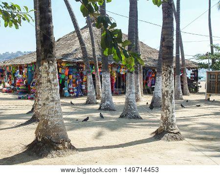ACAPULCO MEXICO - MARCH 11 2006 : Man walk next to a souvenir shop on a beach full of trees in Acapulco Mexico.