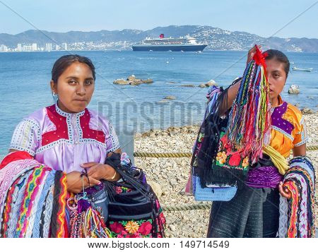 ACAPULCO MEXICO - MARCH 11 2006 : Two Mexican women on a shore with traditional clothing and souvenirs with Queen Mary 2 cruise ship in the background in Acapulco Mexico.